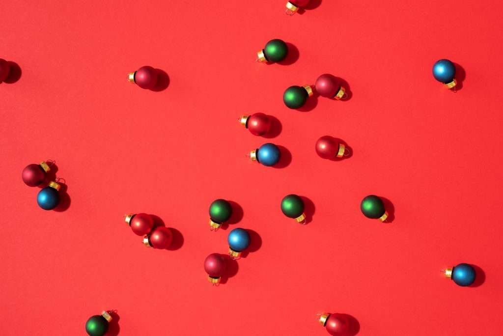 Christmas pattern made of colorful christmas baubles on red background. Flat lay, top view. New year concept